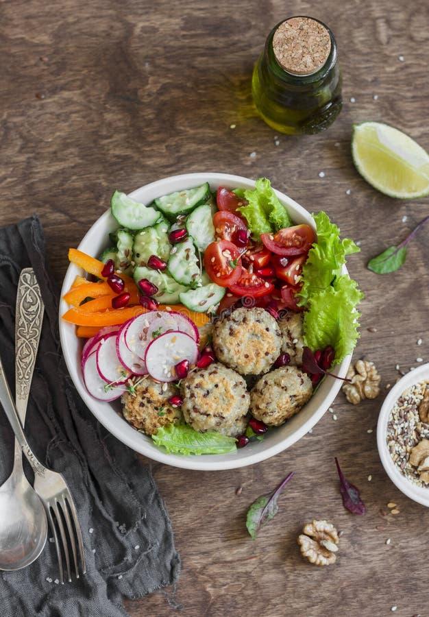 Vegetarierbuddha-Schüssel - Quinoafleischklöschen und Gemüsesalat auf hölzernem Hintergrund, Draufsicht Gesundes, vegetarisches L lizenzfreies stockbild