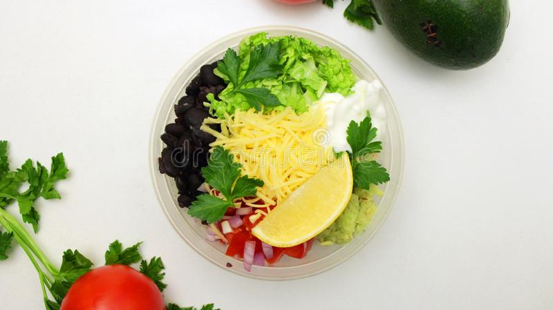 Vegetarina Buddha Bowl Dish with brown rice, avocado, pepper, tomato, cabbage, fresh lettuce salad, olives and lemon. Healthy balanced eating. Top view stock image