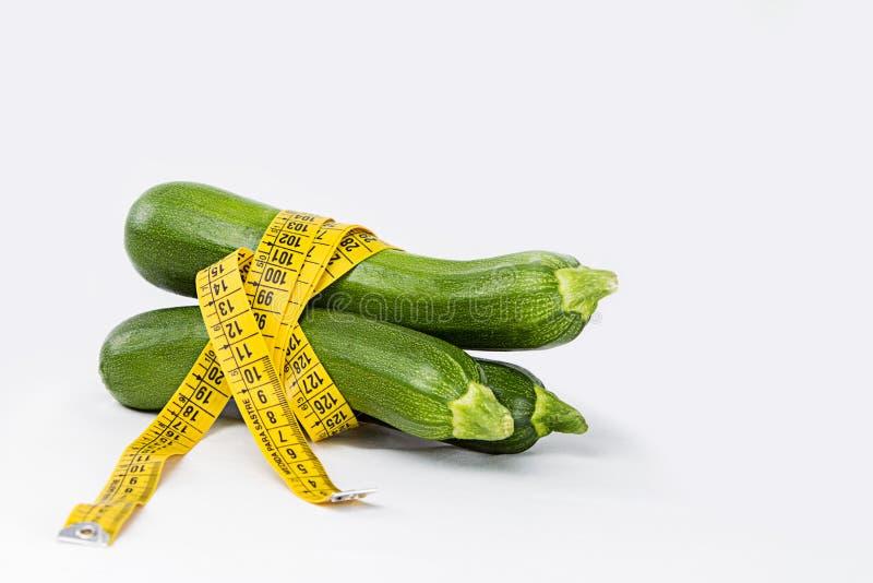 Vegetarisch dieet om gewicht te verminderen Drie vers geplukte die courgettes in een lichaam worden verpakt die bandheerser meten royalty-vrije stock afbeelding