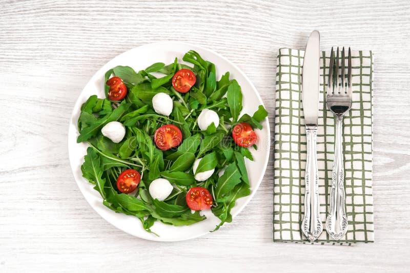 Vegetarisch voedsel en gezond levensstijlconcept - spring salade met kersentomaat, mozarellakaas en arugula op wit plaatla op royalty-vrije stock fotografie
