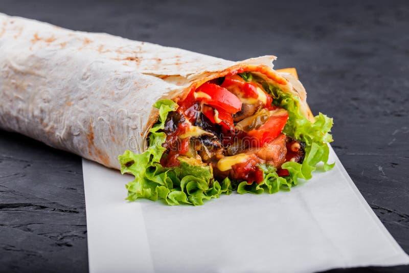 Vegetarische Burrito-omslagen van geroosterde groenten en sla op donkere houten achtergrond royalty-vrije stock fotografie