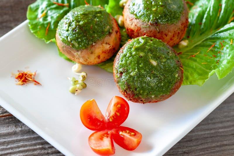 Vegetarische Champignonfleischklöschen mit Pestosoße auf einem Weiß flechten lizenzfreies stockbild