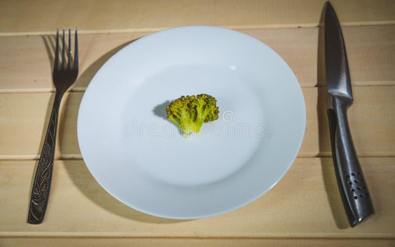 Vegetarische groenten: broccoli, Spruitjes, bloemkool, wortelen en slabonen op een witte plaat en een blauwe achtergrond stock foto