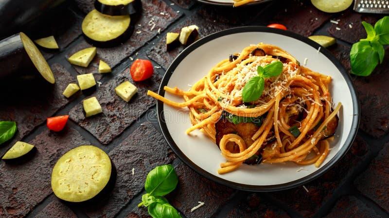Vegetarische Italiaanse alla Norma van de Deegwarenspaghetti met aubergine, tomaten, basilicum en parmezaanse kaaskaas royalty-vrije stock fotografie