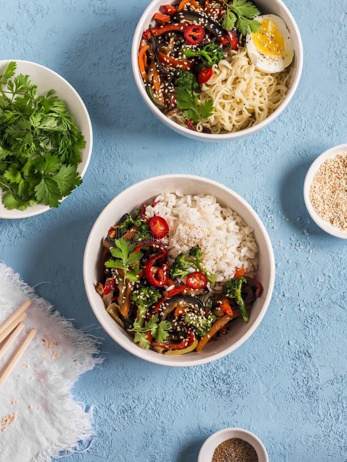 Vegetarische lunchlijst in de Aziatische stijl - de kommen met rijst, noedels, groente bewegen gebraden gerecht Op een blauwe ach stock fotografie