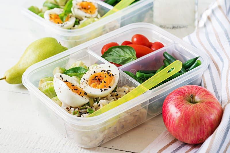 Vegetarische maaltijd prep containers met eieren, spruitjes, slabonen en tomaat stock afbeelding