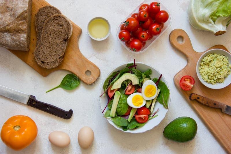 Vegetarische maaltijd prep met eieren, avocado, salade en tomaat Hoogste mening stock foto's