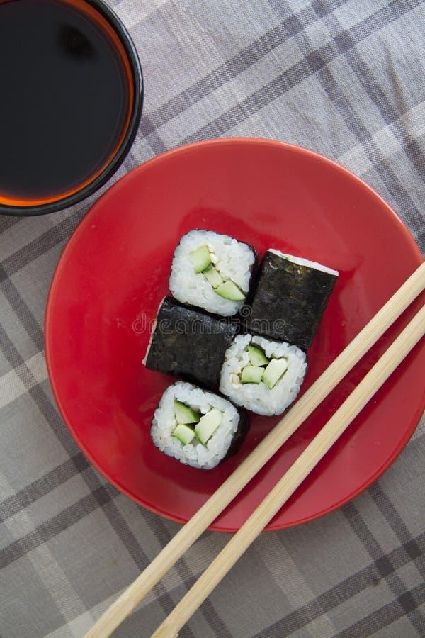 Vegetarische maki op rode plaat met sojasaus stock fotografie