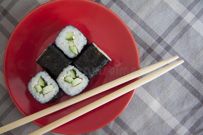 Vegetarische maki op rode plaat met sojasaus stock afbeelding