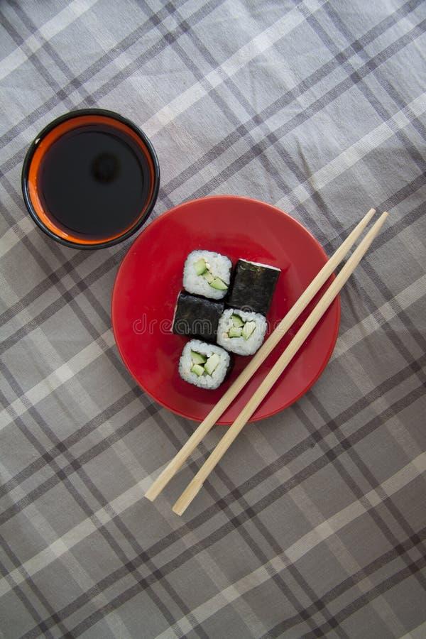 Vegetarische maki op rode plaat met sojasaus stock foto's