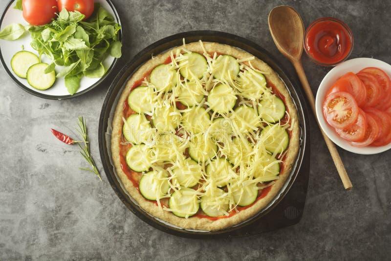 Vegetarische Pizza Garprozess der selbst gemachten Gemüsepizza mit den frischen Bestandteilen lokalisiert auf dunklem Hintergrund lizenzfreies stockbild