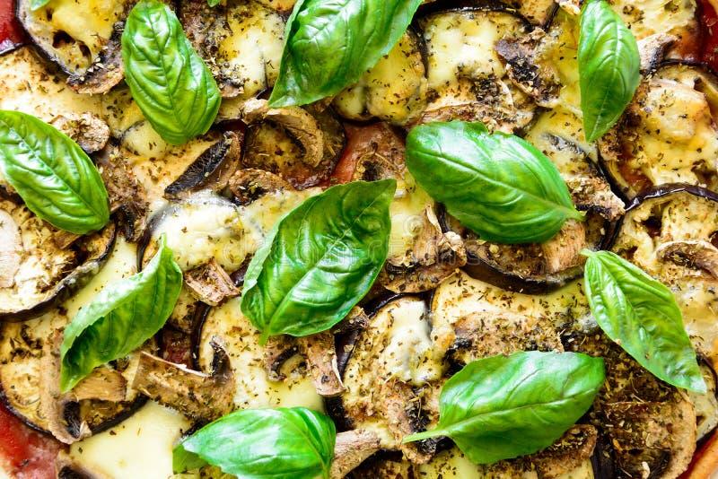 Vegetarische pizza met aubergine, tomaat, paddestoelen en basilicum op houten achtergrond stock foto