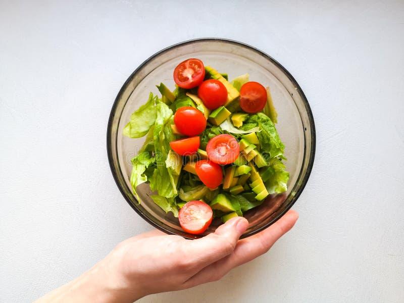 Vegetarische plantaardige salade Verse salade die aan kom in super langzame motie vliegen De Salade van de avocadotomaat royalty-vrije stock afbeeldingen