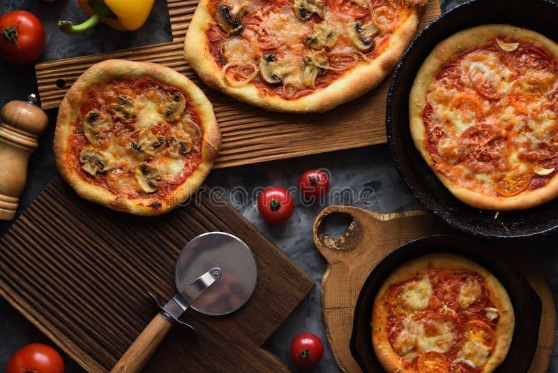 Vegetarische rustieke pizza's Eigengemaakte tomaat en paddestoelpizza's in gietijzerpannen en eiken raad op donkere hoogste menin royalty-vrije stock foto