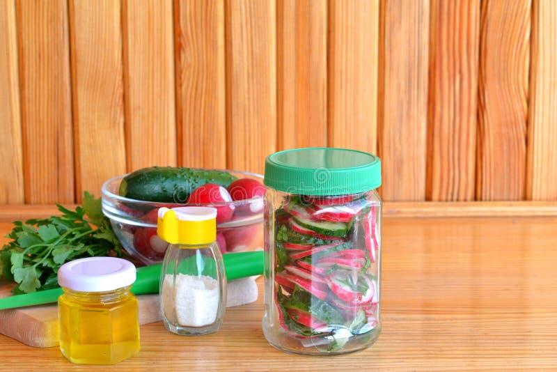 Vegetarische salade in een glaskruik Salade met verse komkommers en radijzen Tendensen in het gezonde eten Reeks voor het koken v royalty-vrije stock fotografie