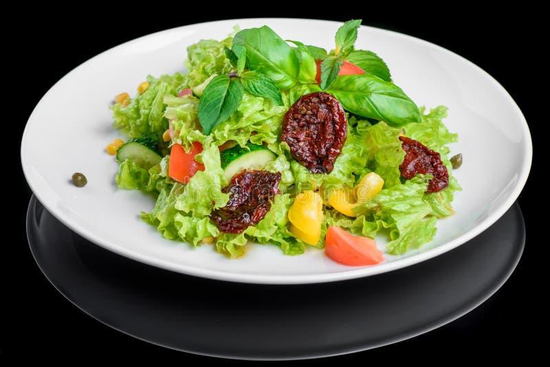 Vegetarische salade met verse en droge die tomaat, peper, basilicum op zwarte achtergrond wordt geïsoleerd royalty-vrije stock afbeelding