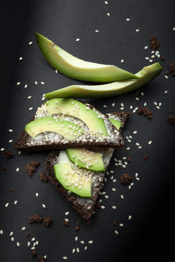 Vegetarische sandwich van zwart brood met avocadoplakken, gesmolten kaas en sesam royalty-vrije stock foto's