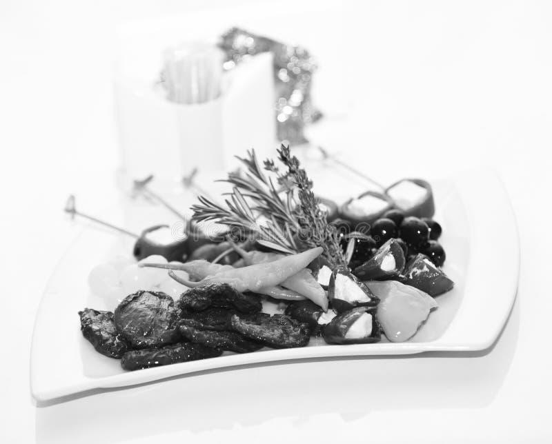 Vegetarische schotel met groenten die met kruiden worden verfraaid Het concept van het braadstukvoedsel Plaat met peper, olijven  stock afbeelding