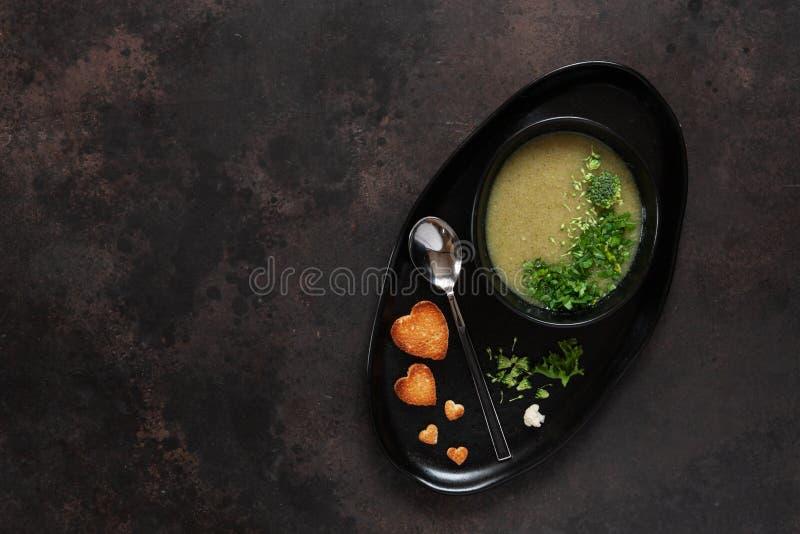 Vegetarische selbst gemachte Cremesuppe des Blumenkohls und des Brokkolis mit Samen, Herzformcrackern und neuem Gewürz Schließen  lizenzfreies stockfoto
