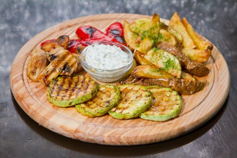 Vegetarischer Grill mit Zucchini, Pommes-Frites, Pilzen, Paprika, weißer Soße und Dill auf hölzerner Platte, Lebensmittelfoto lizenzfreie stockfotos