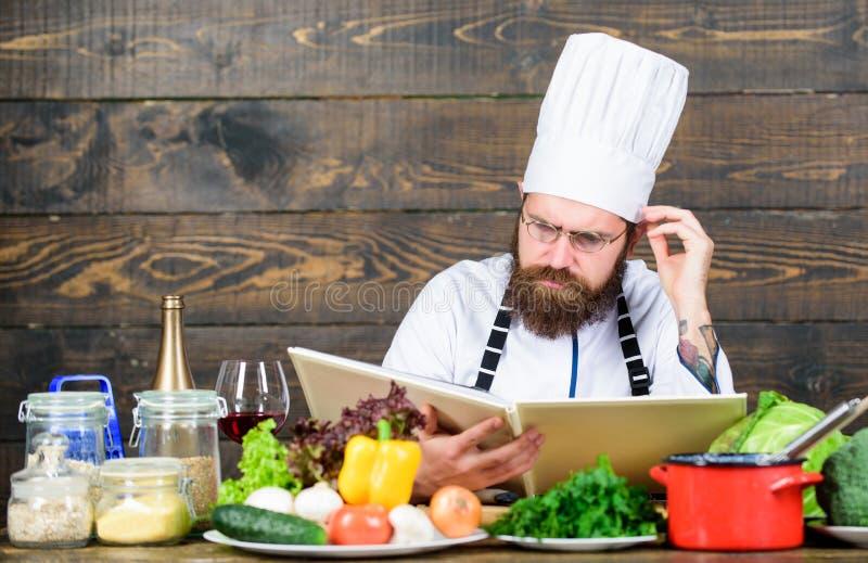 Vegetarisches Rezept B?rtiger Hippie des Mannes las Buchrezept nahe Frischgem?se der Tabelle Kulinarische K?nste Rezept zu kochen lizenzfreie stockfotografie