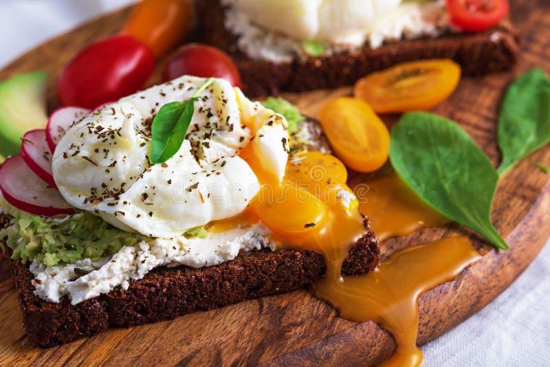 Vegetarisches Toast mit gekochten Eiern mit auslaufendem Yolk, Hüttenkäse, Kirschtomaten, Radieschen, Spinat auf Holzbrett lizenzfreie stockfotografie