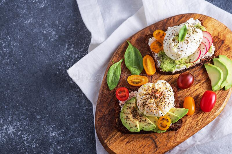 Vegetarisches Toast mit gekochten Eiern, Hüttenkäse, Avocado, Spinat, Kirschtomaten auf Holzbrett auf grauem Hintergrund lizenzfreies stockfoto