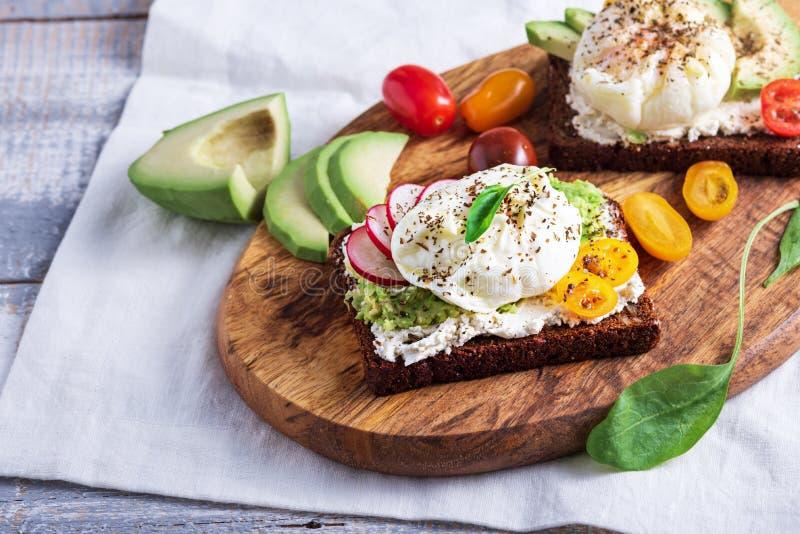 Vegetarisches Toast mit gekochten Eiern, Hüttenkäse, Avocado und Gemüse auf Holzbrett stockbild