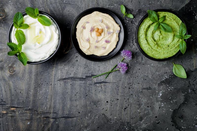 Vegetarisk dopptabell Yoghurtsås eller labneh, hummus, örthummus eller pesto Mitt - östlig mezemellanmåluppsättning royaltyfria foton