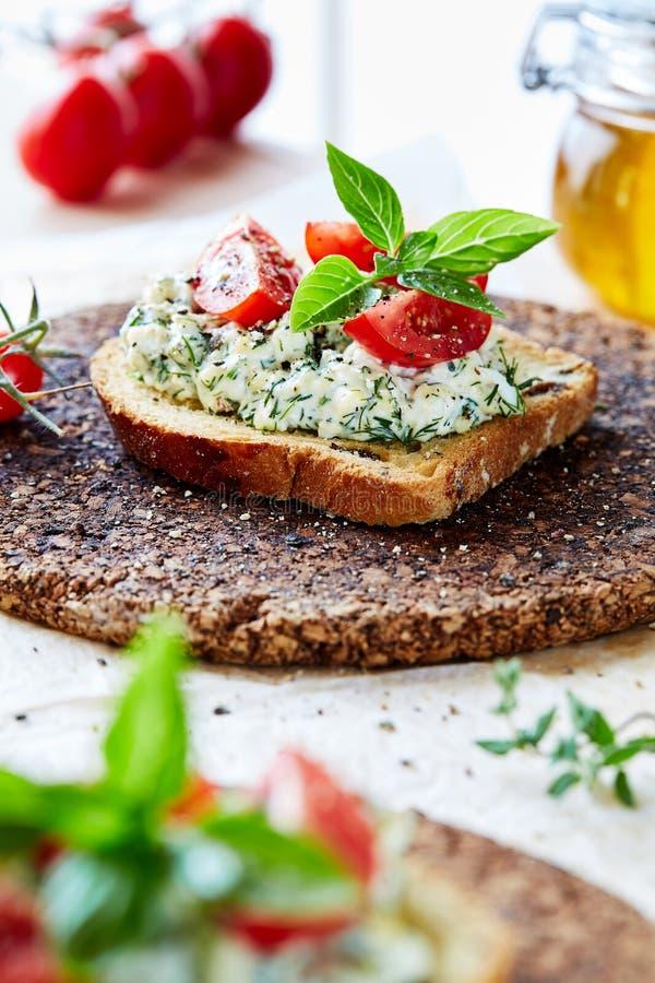 Vegetarisk frukost av mästare Smörgås med äggdeg med dill på rostat bröd Tomater coctail och basilika överst royaltyfri fotografi