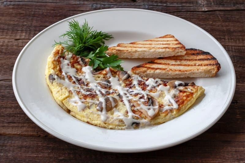 Vegetarisk frukost: förvanskade ägg med champinjoner, gräsplaner och royaltyfri foto