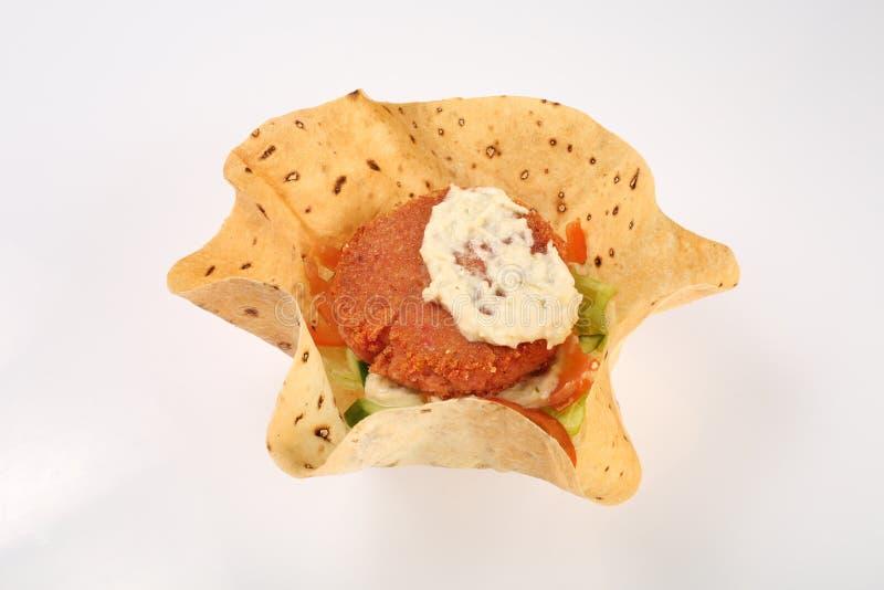Vegetarisk hamburgare i havretortillor med rödbeta, morötter, lökar, kål och grön sallad, kikärtar och avokadon på en platta fotografering för bildbyråer
