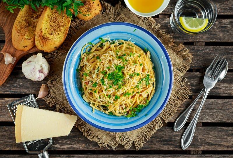 Vegetarisk italiensk pastaspagettiAglio E Olio med vitlökbröd, den röda chiliflingan, persilja, parmesanost och glas av arkivbilder