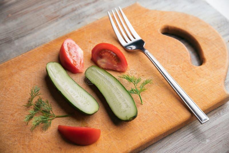 Vegetarisk lunch, gurkor och tomater och gaffel på en träbakgrund arkivbilder