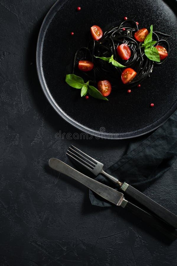 Vegetarisk matr?tt, svart spagetti med basilika och k?rsb?rsr?da tomater Svart bakgrund, b?sta sikt royaltyfri fotografi