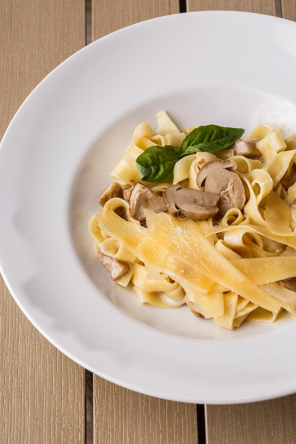 Vegetarisk pastamaträtt för tagliatelle med champinjoner som dekoreras med basilika Läcker lunch med pasta och vita champinjoner arkivfoto