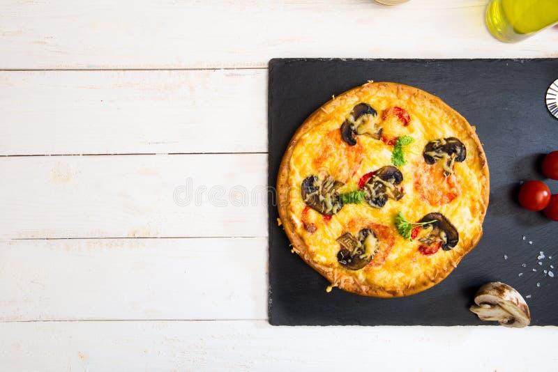 Vegetarisk pizza med champinjoner tjänade som på vit trätabell- och svartstenyttersida ordna till för att äta royaltyfria foton