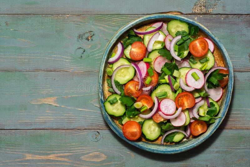 Vegetarisk sallad av nya grönsaker på en grön träbakgrund Bästa sikt, kopieringsutrymme arkivbild