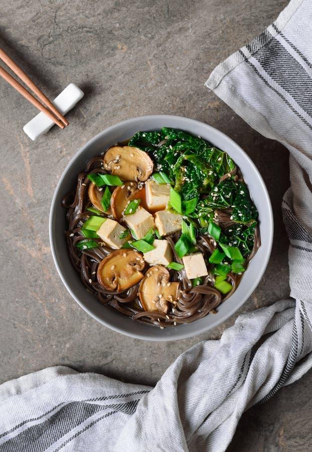 Vegetarisk soppa med grönkålchampinjoner och sobanudeln royaltyfria bilder