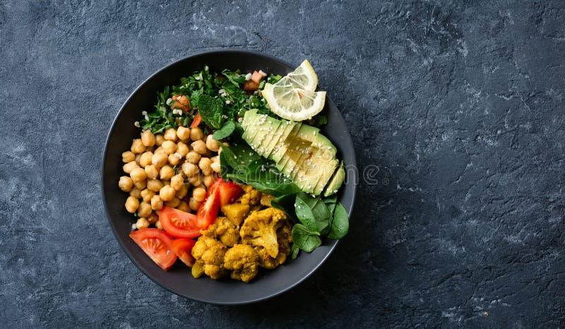 Vegetarisk sund allsidig mat Aloo gobi, kikärtar, tomat, avokado, tabulesalladspenat för Buddhabunke arkivbild
