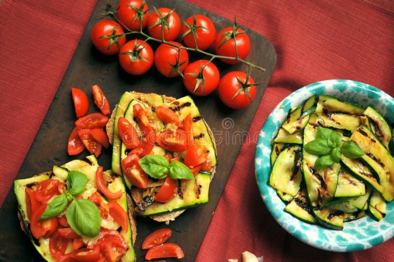 Vegetarisk sund mat med den grillade zucchinin och tomaten arkivbild