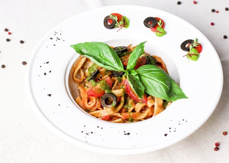 Vegetarisk tomatpasta med pestosås, svarta oliv och basilika royaltyfri fotografi