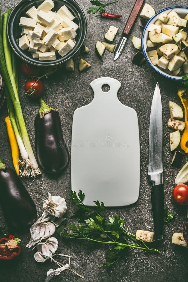 Vegetariska matingredienser med grönsaker, örter, fetaost, kryddor och kökkniven runt om skärbrädan, bästa sikt, ram royaltyfri foto