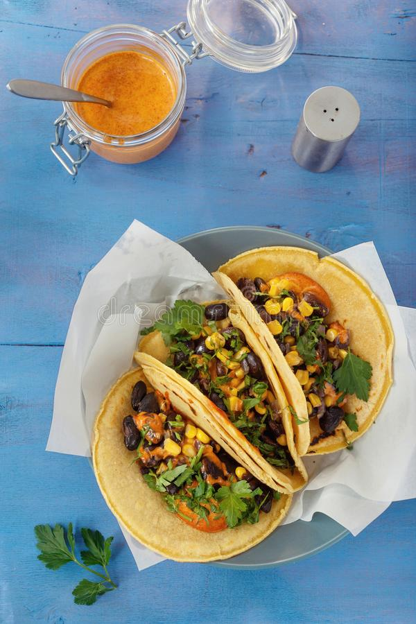 Vegetariska svarta bönor för tacohavretortillor konserverar kryddig sa för peppar arkivbild