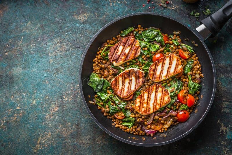 Vegetariskt matbegrepp Sund linsmaträtt med spenat och stekt ost i matlagningpanna på lantlig bakgrund med ingredienser royaltyfria bilder