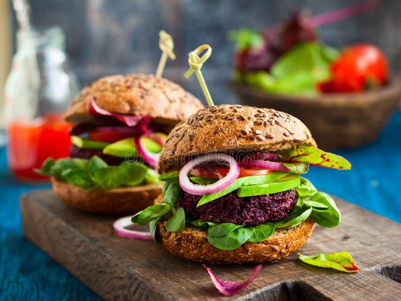 Veggie beet and quinoa burger. With avocado stock photography