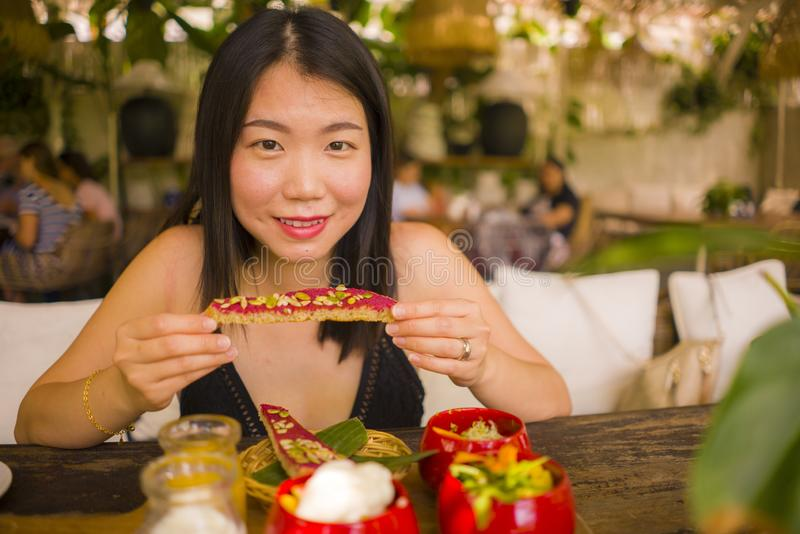 Veggie brunch . natural lifestyle portrait of young happy and beautiful Asian Chinese woman eating outdoors having organic stock images