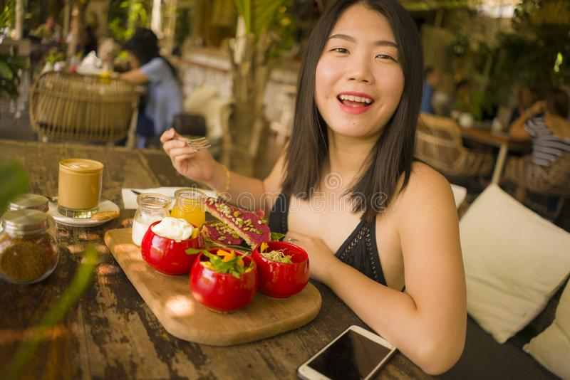 Veggie brunch . natural lifestyle portrait of young happy and beautiful Asian Chinese woman eating outdoors having organic stock image