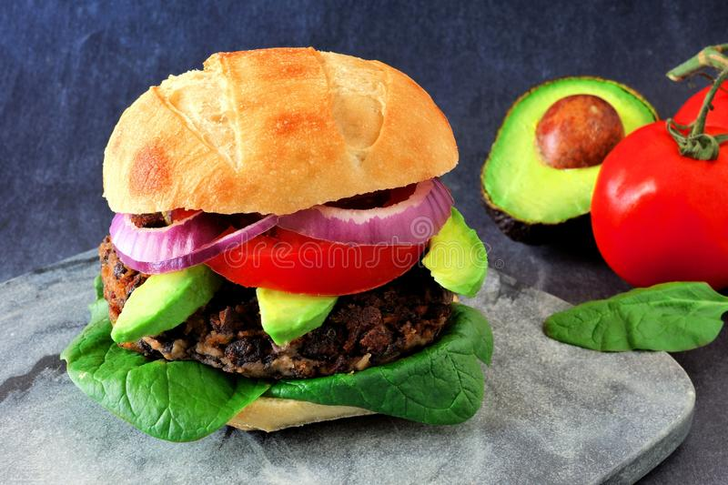 Veggie burger with avocado and spinach on a dark background. Bean and sweet potato veggie burger with avocado and spinach against a dark background stock images