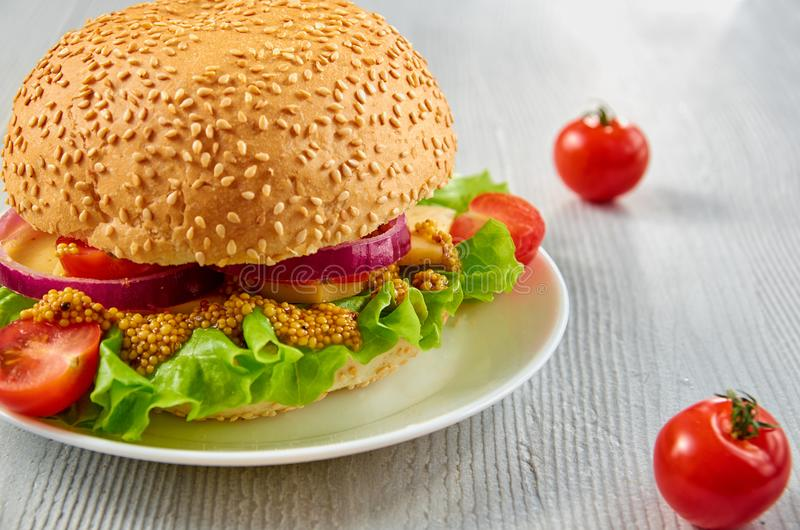 Veggie burger with salad, onion rings decorated with fresh cherry tomatoes on the gray concrete background with free copy space royalty free stock photography